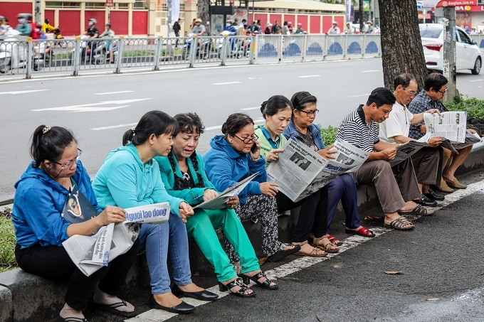 Parents read newspapers as they wait for their children outside an exam center in Ho Chi Minh City. Photo by VnExpress/Thanh Nguyen.