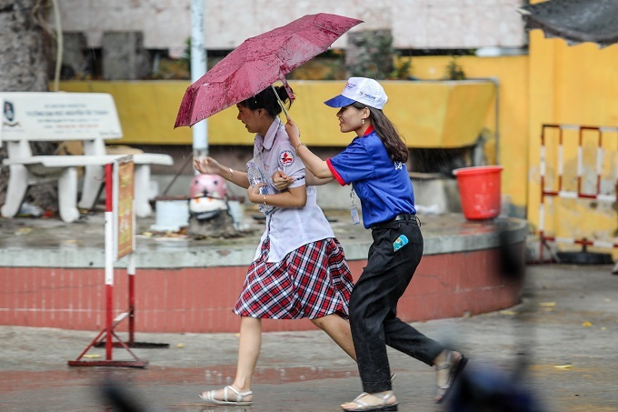 A support staff protects a student from the rain at an exam center in Ho Chi Minh City. Photo by VnExpress/Thanh Nguyen.