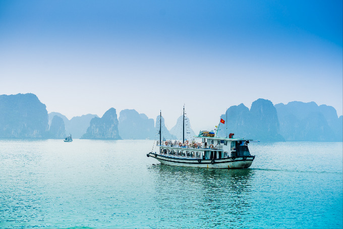 A cruise ship near rock islands in the famous Ha Long Bay in the northern province of Quang Ninh. Photo by ShutterShock/Tung Duong