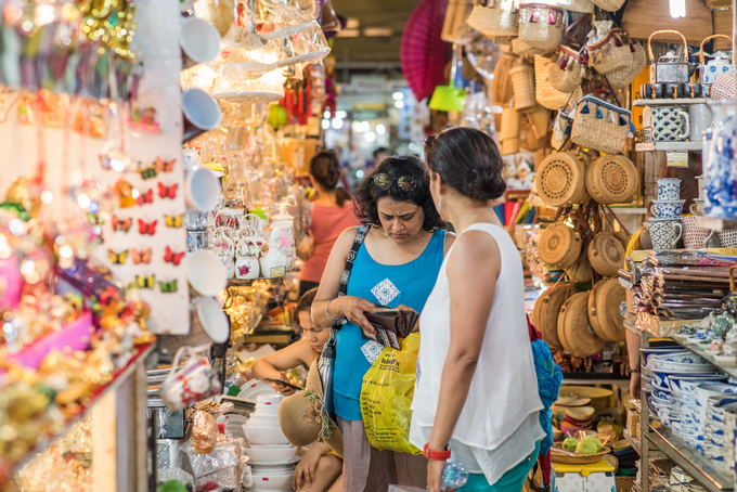 Foreign tourists buy souvenirs inside Ben Thanh Market in downtown Saigon. Photo by Shutterstocks/diemtinh
