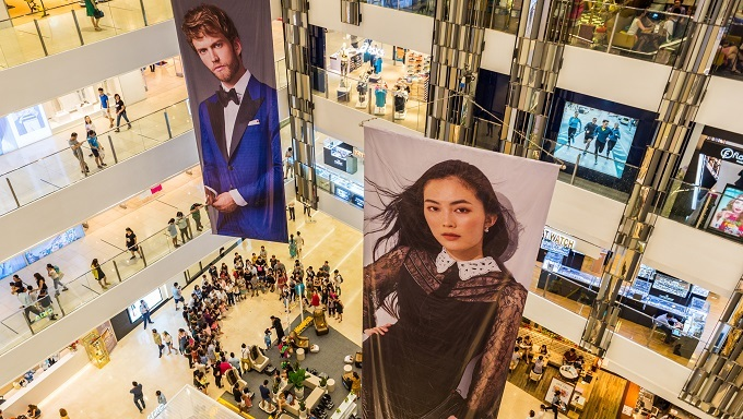 Multistory interior of Saigon Center with two large advertising placards showing portraits of models. Photo by Shutterstock/David Bokuchava.