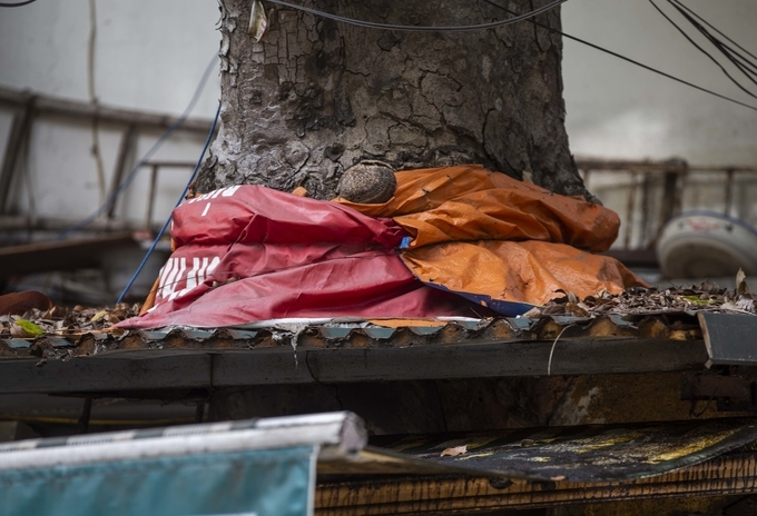 Residents wrap a root with canvas material to prevent flooding when the rain comes. Photo by Duc Tung