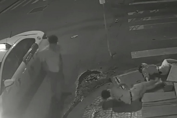 A screenshot from CCTV camera footage shows a taxi driver looking at a man and a woman he crashed into in HCMC, June 25, 2019. As he left them there and the no one stopped to help, the woman died later.