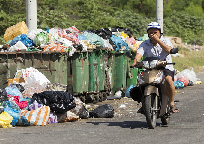 A man covers his nose as he drives past piles of trash on a street of Da Nang during the protest in early July, 2019 that saw locals blocked roads to the citys sole landfill. Photo by VnExpress/Nguyen Dong