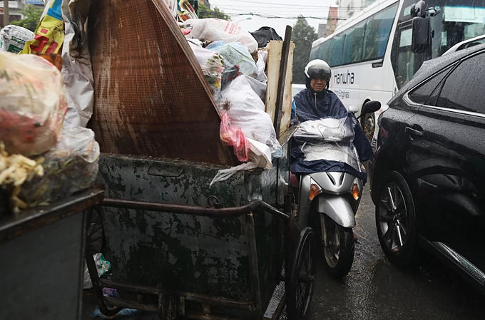 A motorbike driver rides next to garbage trolleys in Nam Tu Liem District, Hanoi. Photo by VnExpress.