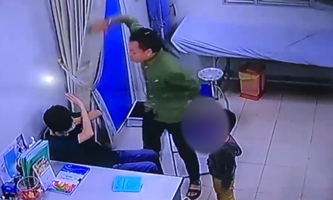 A screenshot from camera footage of Hanois Saint Paul Hospital shows a doctor (L) being hit by a patients father as he was explaining the boys head wounds, April 13, 2018.