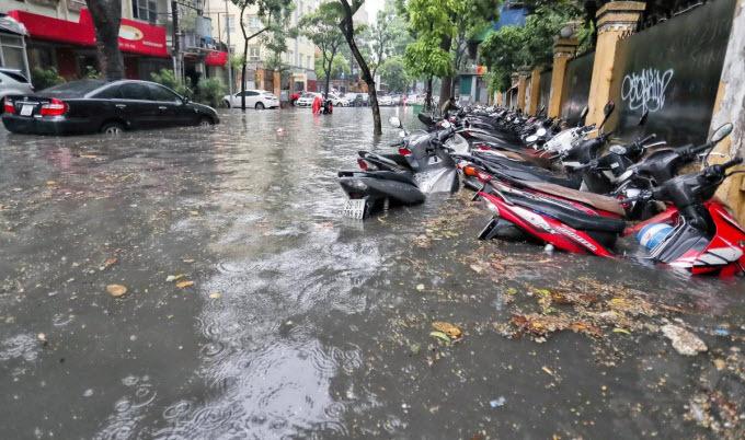Commuters struggle as downpour floods Hanoi streets - 1
