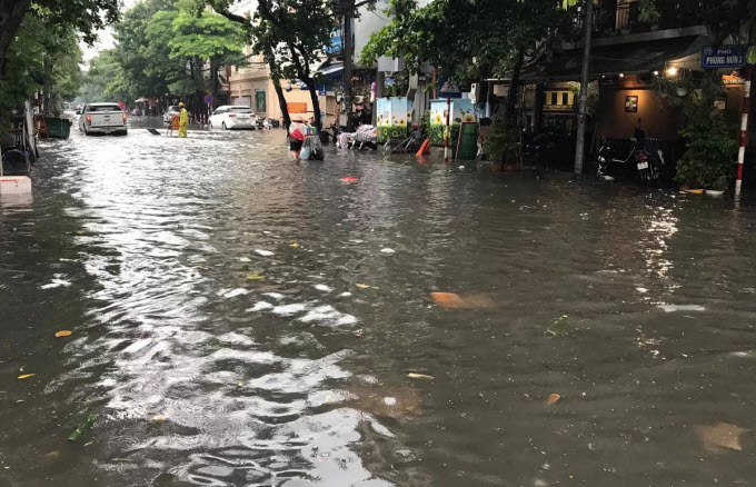 Commuters struggle as downpour floods Hanoi streets - 4