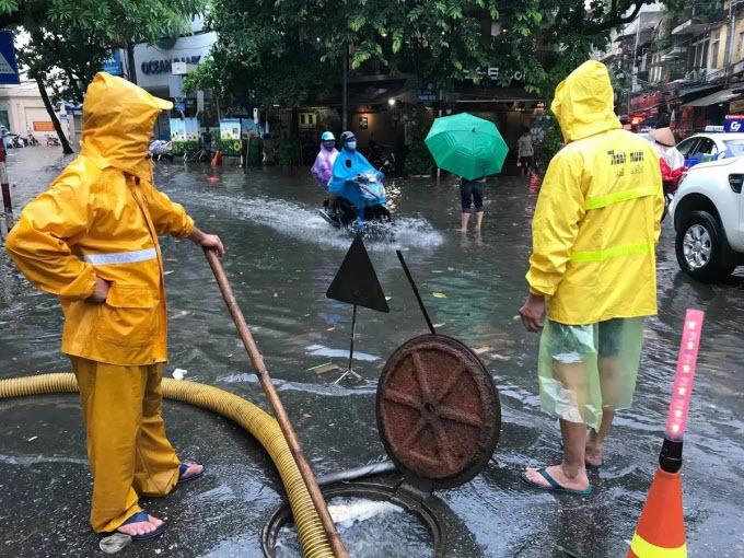Commuters struggle as downpour floods Hanoi streets - 5