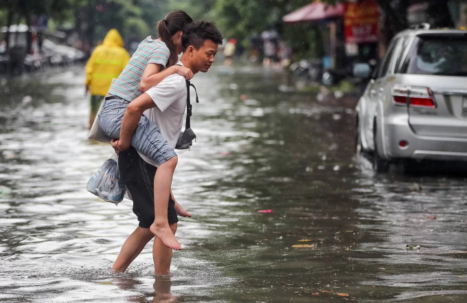 Commuters struggle as downpour floods Hanoi streets - 2