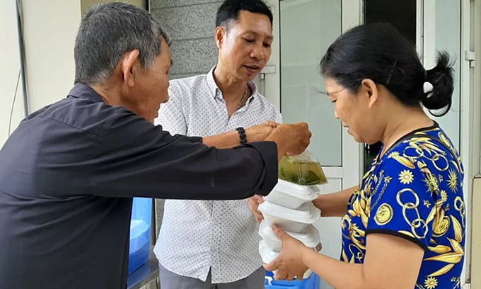 Nguyen Van Chu (L) delivery free meals at the Institute of Medical Radiology and Oncology in Hoang Mai District, Hanoi.