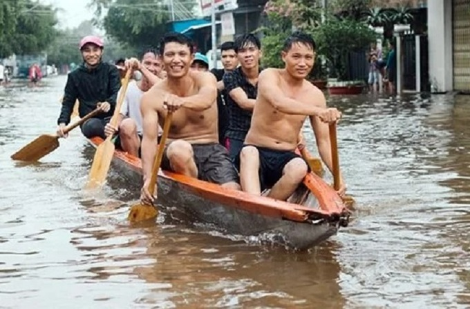 Several people use a boat to traverse a flooded street of Phu Quoc Island, Kien Giang Province. Photo by Riko.