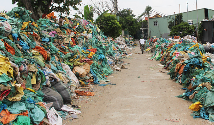 Trash piles up on the two sides of a road in Minh Khai Village. Photo by VnExpress/DatNguyen