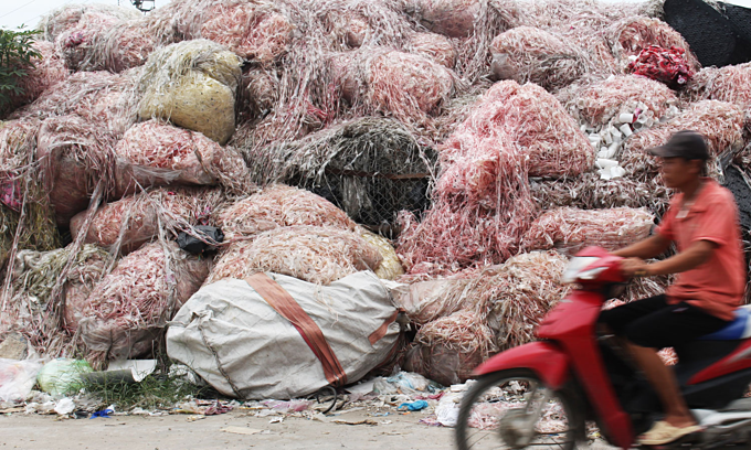 A man rides past piles of trash in Minh Khai Village. Photo by VnExpress/Dat Nguyen