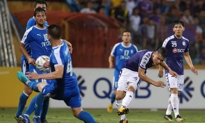 Nguyen Quang Hai (R) dribbles past three Altyn Asyr defenders to score Vietnams second goal in the AFC Cup interzone semifnal in Hanoi, August 20, 2019.