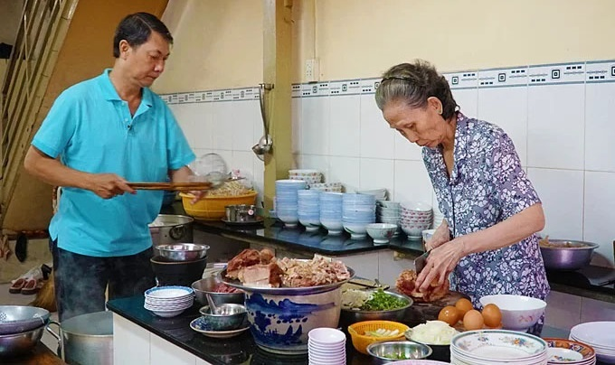 Sau Dan (R) and her younger brother prepare the ingredients for pho as it was first served by her father 77 years ago. Photo by VnExpress/Di Vy.
