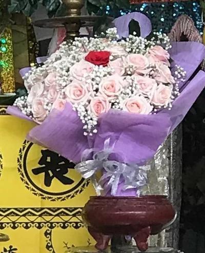 An places a wedding bouquet  before his fiancé's portrait. Photo by VnExpress/Bich Thuc.
