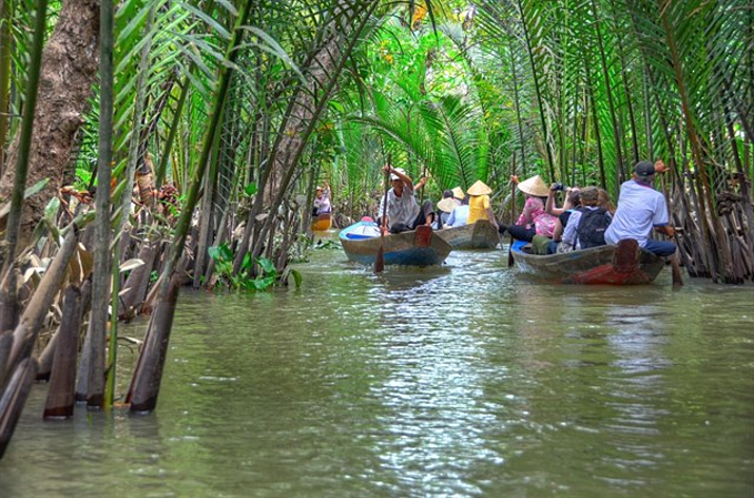 People take boat rides under coconut canopies along canals that zigzag through the small islet. Photo acquired by VnExpress.