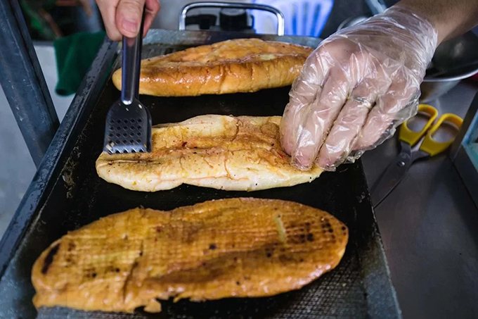 A cook is pressing down the baguette while grilling it. Photo by VnExpress/Dinh Dinh.