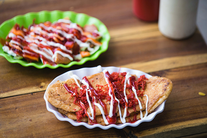 Two plates of grillled baguette with beef jerky, ketchup, hot sauce and mayonnaise on top. Photo by VnExpress/Dinh Dinh.