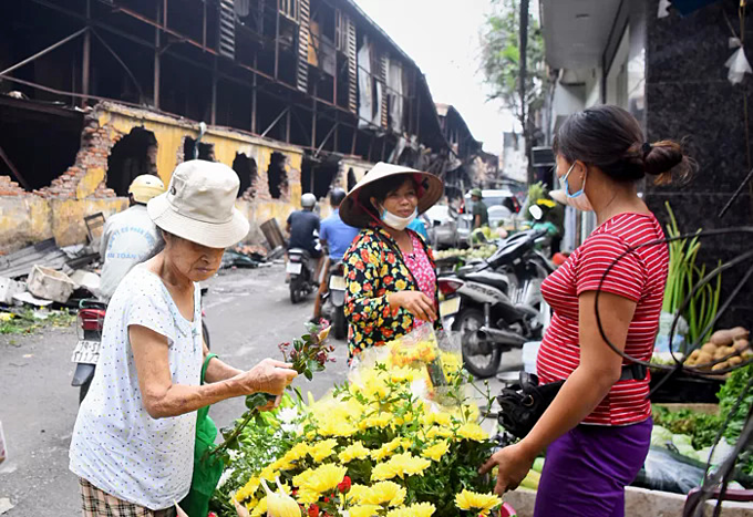 Life goes on outside Rang Dong light bulb warehouse (L) in Hanoi, August 30, 2019. Photo by VnExpress/Giang Huy.