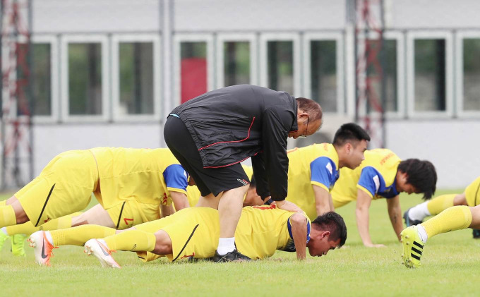 The team continues training on Monday as Coach Park helps in a push-up exercise.