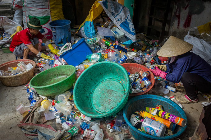 Du (left) and his wife, Vo Thi Cuc, 51 sort trash near their home on August 5, 2019. Photo by VnExpress/Thanh Nguyen.