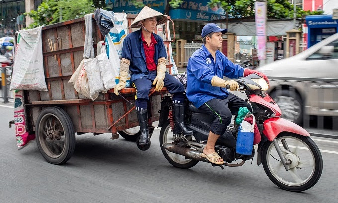 Tran Manh Du (L) and his son Tran Manh Duy on their way to collect garbage in Binh Thanh District, HCMC, July 2019. The vehicle they use, a trademark of unofficial waste collectors like them, is a motorbike with a 660-liter trailer attached to it. Photo by VnExpress/Thanh Nguyen.