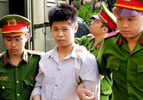 Nguyen Huu Tinh is escorted by police officers to the court where he receives death penalty for murders. Photo by VnExpress/Ky Hoa.