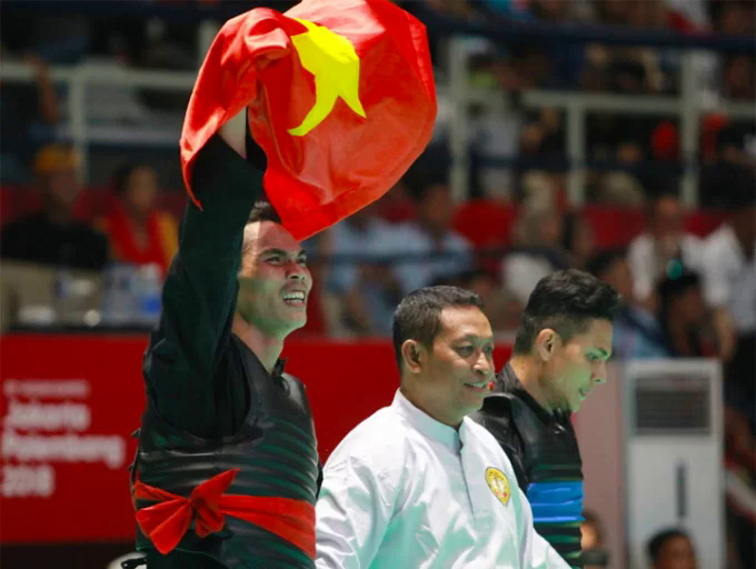 Tran Dinh Nam raises the national flag after winning a gold medal for Vietnam in Pencak Silat at ASIAD 2018. Photo by VnExpress/Xuan Binh.