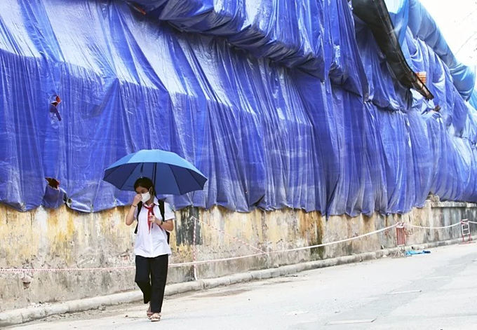 A student wearing a mask walks in an alley near the Rang Dong warehouse. Photo by VnExpress/Tat Dinh.