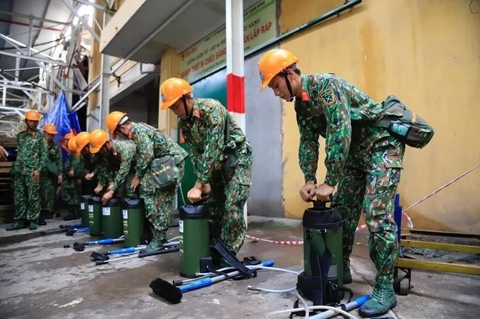 Military personnel prepare their gears before entering the warehouse. They would clean up the site, collect the waste and decontaminate the area. As theres so much to clean, it would take quite a while, said Nguyen Van Bong, head of the Search and Rescue Department of the Hanoi Capital High Command.