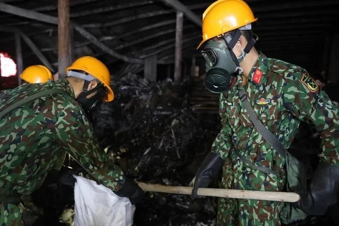 Two soldiers with masks clean up the two floors of the warehouse and collect waste to be disposed of.