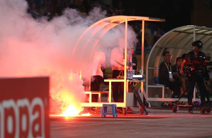 The flare came from Nam Dinh fans at the 56th minute of the game. It travelled from stand B to stand A, hit the legs of a female fan, bounced back to the referee zone meters away and then burned.