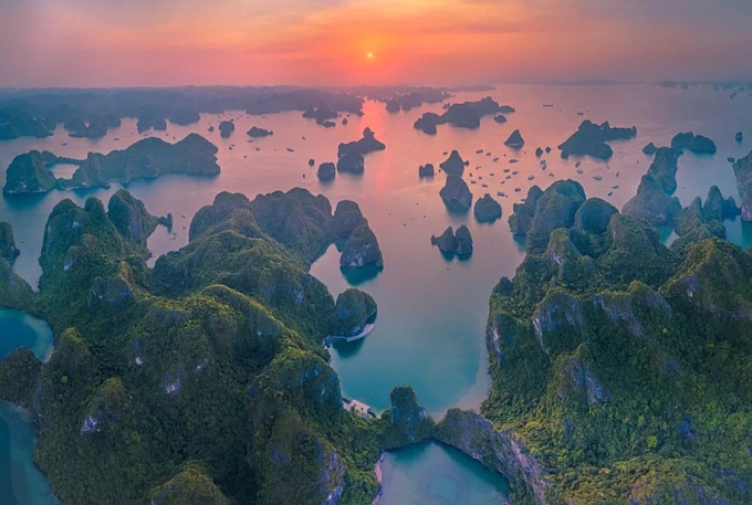 Sunset over the bay. Most of the islets in Ha Long Bay are uninhabited; many of them are inaccessible to human visitors due to their sheer limestone cliffs.