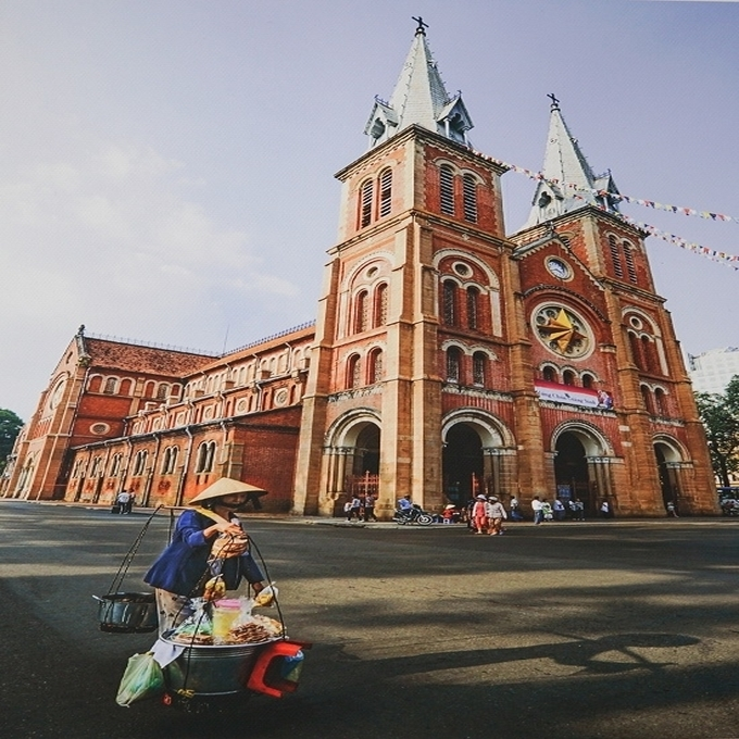 Street vendors work around one of Saigon's iconic buildings, the Notre Dame Cathedral as there are many tourists and visitors in this part of Saigons downtown.