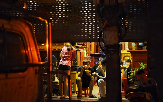 Customers sit inside the half-closed door of a restaurant in Hanoi, after midnight in September 2019. Photo by VnExpress/Giang Huy.
