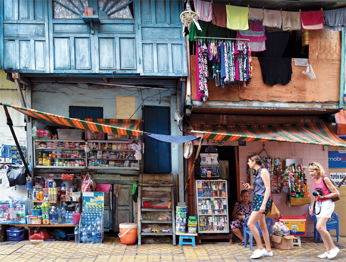 Tourists walk past makeshift shops and residences on another part of the sidewalk life on Bui Vien Street in 2016.