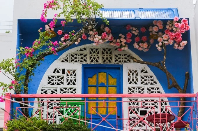 The café's façade of white, cobalt blue and pink are inspired by colors on the Greek island, as are the real bougainvillea flowers and fake roses that adorn a painted arch on the third floor's balcony.  People in the Mediterranean love to plant many flowers in front of their house, mainly red and pink flowers, he said.