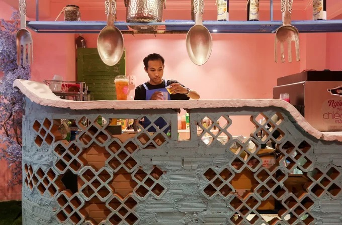 The café's bar has a deliberately created rough earth look, using a softer shade of pink that contrasts with violet trellis and flowers in a corner. Prices for drinks range from VND35,000 to VND80,000 ($1.5 - 3.4)
