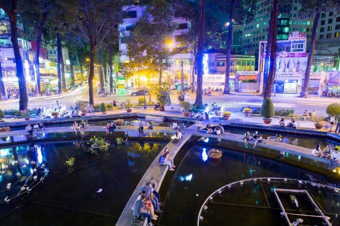 People hang out at night at a circular pond at the intersection of Pham Ngoc Thach and Vo Van Tan streets in District 3 that locals call the Turtle Lake. Photo by Shutterstock/Dinh Nguyen.
