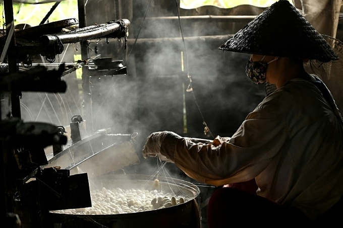 Dozens of workers in Vietnams silk workshops gently unwind the fibre from silkworm cocoons through clouds of rising steam. Photo by AFP / Manan Vatsyayana.
