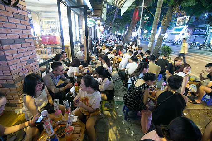 Customers, most are youngsters, enjoy the drink on Hanois Nguyen Huu Huan Street. Photo by VnExpress/Tunh Dinh.