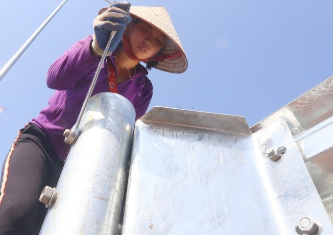 Hoang Thi Phan, a native from the northern province of Yen Bai, installs steel guardrail fences. To keep up with the opening day, Phan and her peers have been working through the lunch time these days, even through the night.