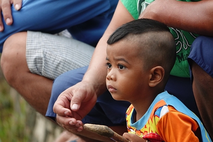 A Khmer boy glues his eyes to the race at the festival.