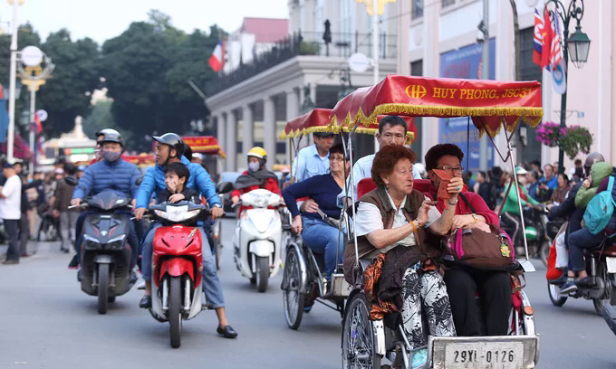 Foreign tourists take a cyclo ride in Hanoi in February 2019. Photo by VnExpress/Pham Duong.