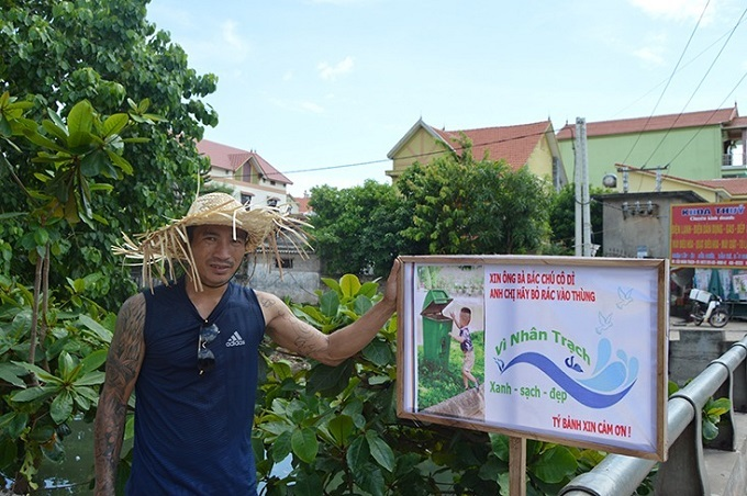 Dinh Ty stands by a billboard he sets up to call local residents in Nhan Trach Commune to put garbage in trash can for a green, clean and beautiful environment. Photo coutersy of Quang Binh Provinces online newspaper.