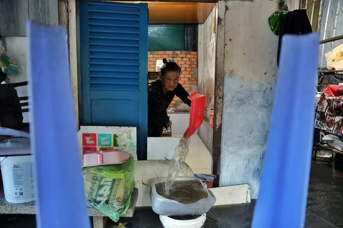 Nguyen Thi Bay, 78, pours water out of her house in District 2, Saigon, September 29, 2019. Photo by VnExpress/Huu Khoa.