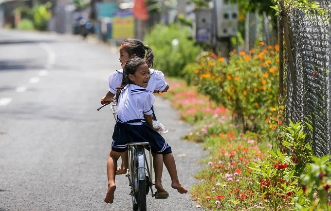 Two sisters tour the neighborhood by bike after school, still in their uniform.