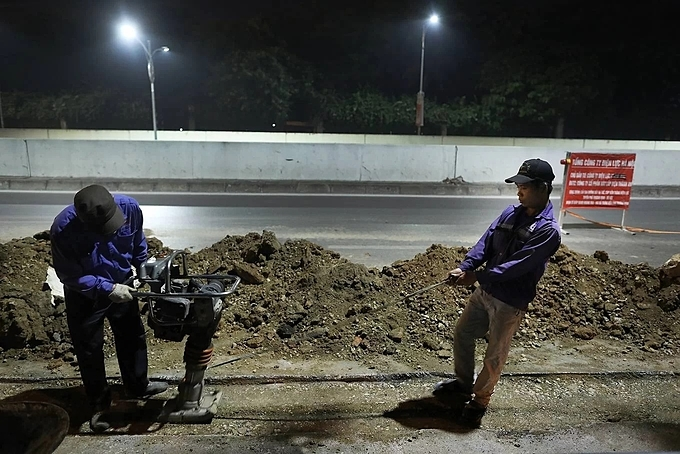 Duc, 43 (right), a construction worker and his colleague are working at a site on Dai Co Viet Street at 2 a.m.Their job is essentially to clean up the mess after a construction site has finished, including polishing the road, backfilling the holes on the ground, and reinstalling the electric wires. People like Duc have to work when everybody else is not at the site.Duc starts working at 11:30 p.m., when his wife and children are sleeping sound in the house in Van Dien in the outskirts of Hanoi.When the shift ends at 5:00 am, Duc and his fellow construction workers come home to have breakfast and immediately go to another digging and cleaning gigs at another construction site.